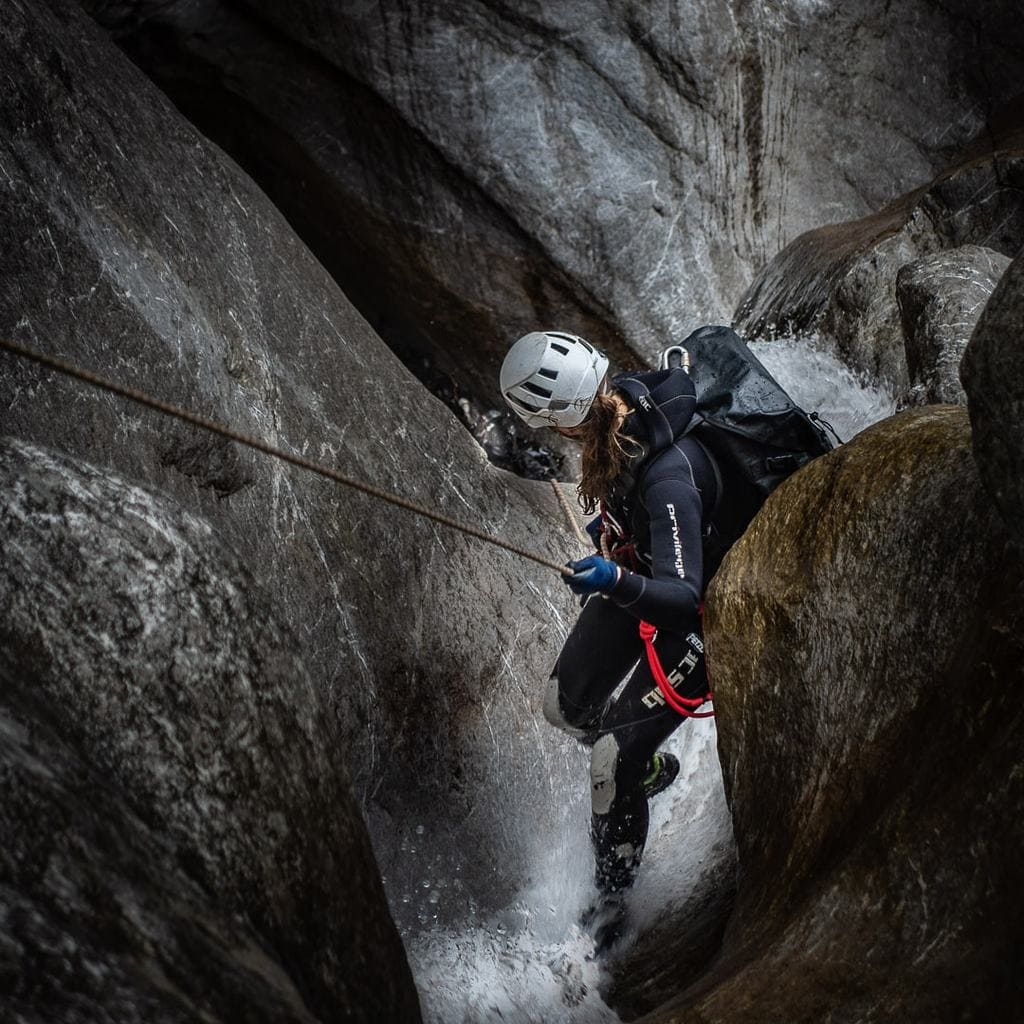 Cave explorer descening with rope with waterproof backpack