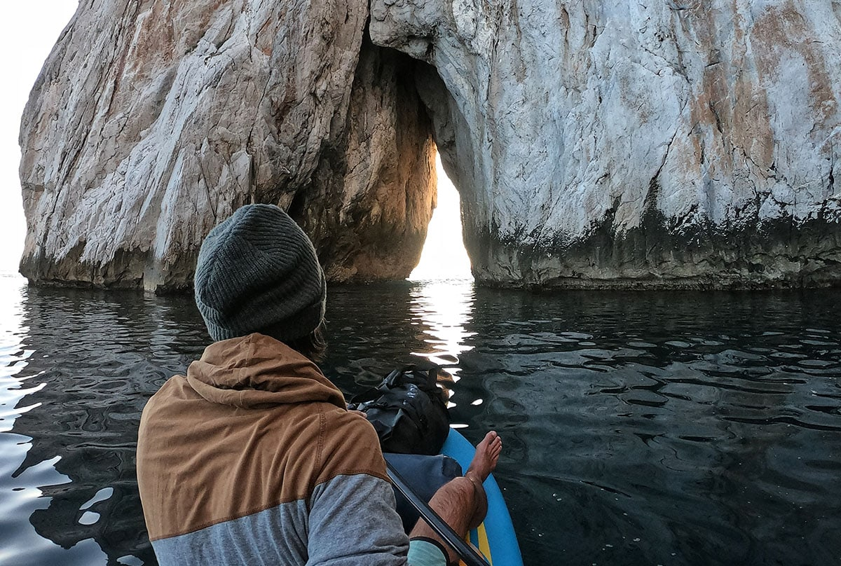 Man paddling towards a natural arch