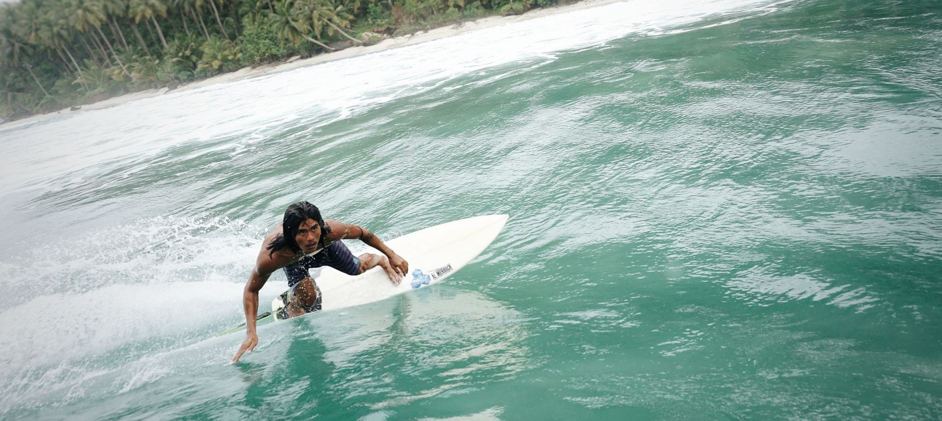 Surfer leaning into a wave in Mentawai islands