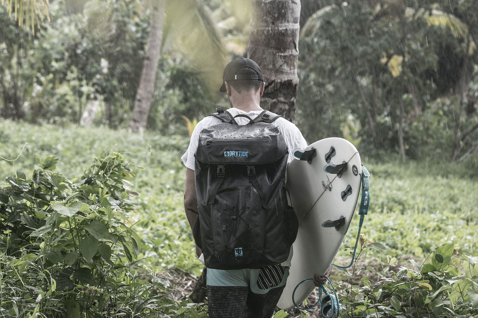 Surfer trekking through the jungle carrying a surfboard and a waterproof backpack