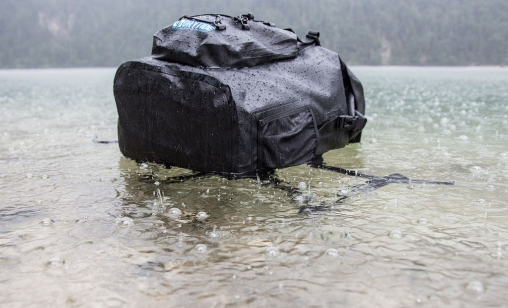 Waterproof laptop backpack floating on lake surface